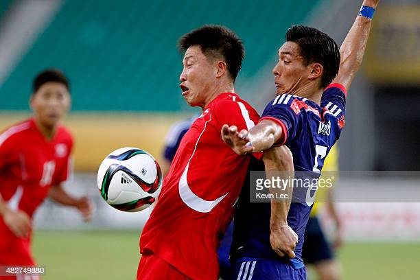 Japan's Tomoaki Makino and DPR Korea's Kang Kuk Chol compete for the ball during EAFF East Asian Cup 2015 final round on August 2 2015 in Wuhan China