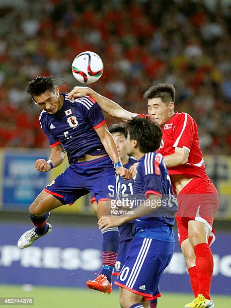 Japan's Tomoaki Makino and DPR Korea's Kang Kuk Chol competes for the ball during EAFF East Asian Cup 2015 final round on August 2 2015 in Wuhan China