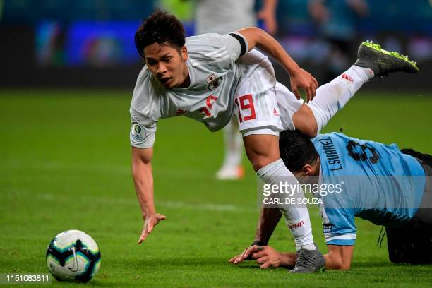 Japan's Tomoki Iwata and Uruguay's Luis Suarez battle for the ball during the Copa America football tournament Group C match between Uruguay and...