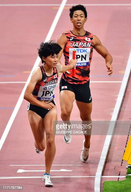Japan's Tomoyo Tamura passes the baton to Saki Takashimi in the Mixed 4 x 400m Relay heats at the 2019 IAAF World Athletics Championships at the...