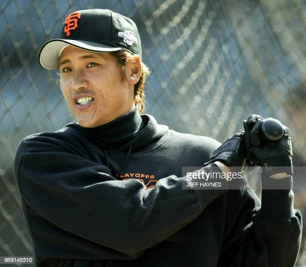 Japan's Tsuyoshi Shinjo of the San Francisco Giants warms up 16 October 2002 during his team's workout at Pacific Bell Park in San Francisco CA The...