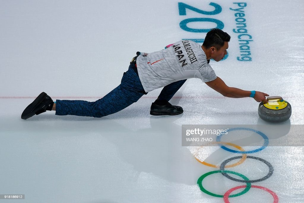 Japan's Tsuyoshi Yamaguchi throws the stone during the curling men's round robin session between Norway and Japan during the Pyeongchang 2018 Winter Olympic Games at the Gangneung Curling Centre in Gangneung on February 14, 2018. / AFP PHOTO / WANG Zhao