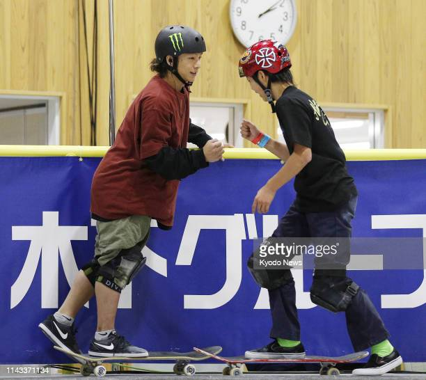 Japan's twotime Olympic snowboard silver medalist Ayumu Hirano bumps fists with competitor Yuro Nagahara during the men's park final at the national...