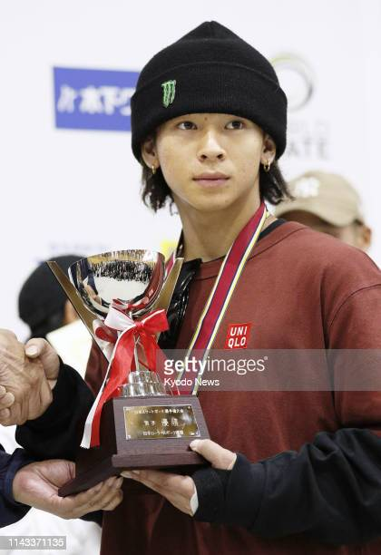 Japan's twotime Olympic snowboard silver medalist Ayumu Hirano holds his trophy after winning the men's park event at the national skateboarding...