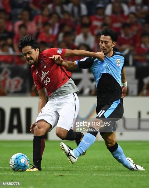 Japan's Urawa Reds midfielder Akihiro Ienaga fights for the ball with Kawasaki Frontale midfielder Shinzo Koroki during the AFC Champions League...
