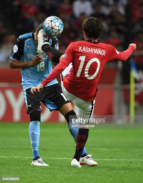 Japan's Urawa Reds midfielder Yosuke Kashiwagi fights for the ball with Kawasaki Frontale defender Elsinho during the AFC Champions League...