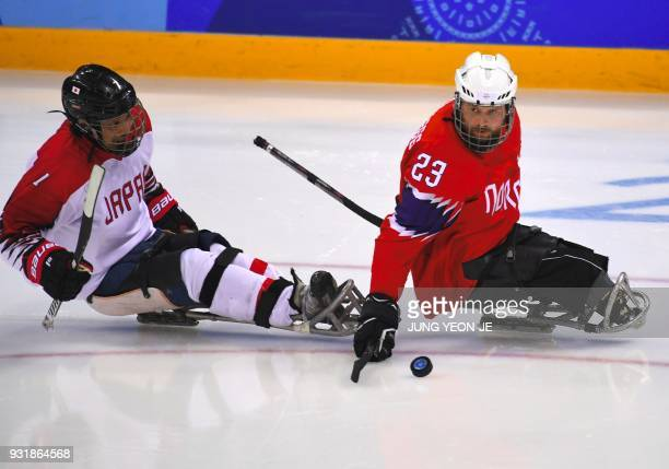Japan's Wataru Horie and Norway's Jan Roger Klakegg fight for the puck during the ice hockey classification game between Norway and Japan at the...