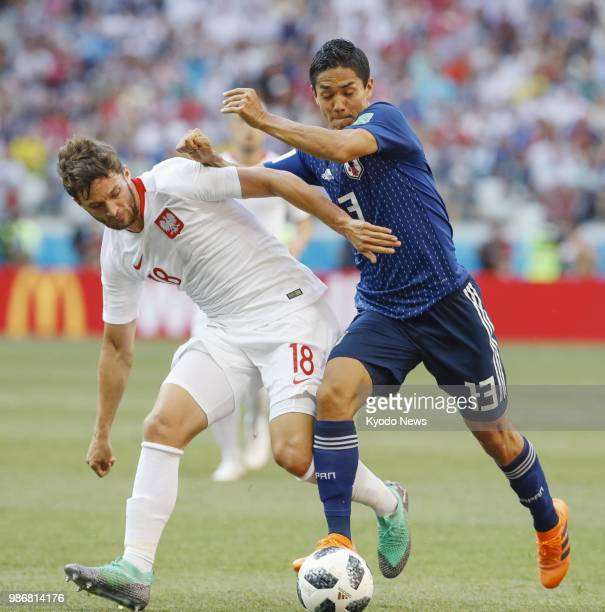 Japan's Yoshinori Muto and Poland's Bartosz Bereszynski vie for the ball during the first half of a World Cup group stage match at Volgograd Arena in...