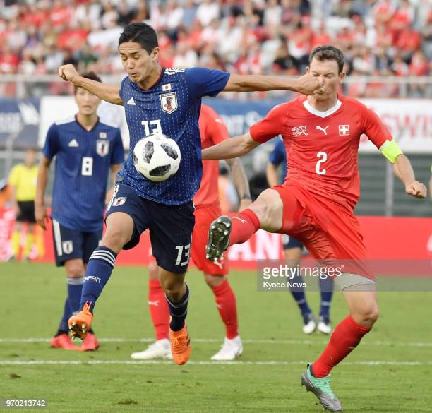 Japan's Yoshinori Muto and Switzerland's Stephan Lichtsteiner compete for the ball during the second half of a preWorld Cup friendly in Lugano...