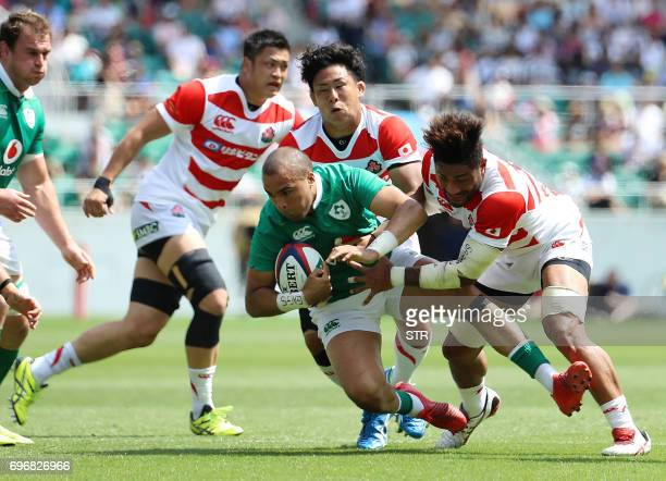 Japan's Yoshitaka Tokunaga and Amanaki Lelei Mafi tackle Ireland's Simon Zebo during their rugby union Test match in Shizuoka on June 17 2017 Ireland...