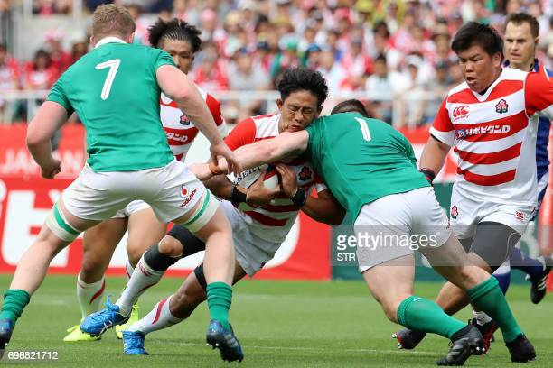 TOPSHOT Japan's Yoshitaka Tokunaga is tackled by Ireland's Cian Healy and Dan Leavy as Japan's Heiichiro Ito looks on during their rugby union Test...