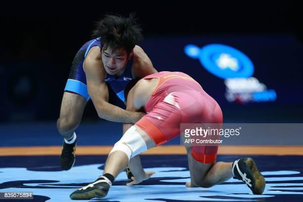 Japan's Yuhi Fujinami challenges Georgia's Zurabi Erbotsonashvili during the men's freestyle wrestling 70kg category bronze medal final at the FILA...