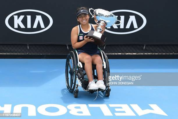 Japan's Yui Kamiji celebrates with the winning trophy after beating Netherland's Aniek Van Koot during their women's wheelchair singles match on day...