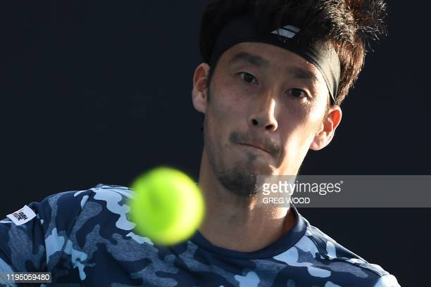 Japan's Yuichi Sugita hits a return against France's Elliot Benchetrit during their men's singles match on day two of the Australian Open tennis...