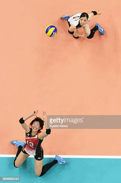 Japan's Yuki Ishii and Arisa Sato chase the ball during the second set of their preliminary round match against Argentina in women's volleyball at...