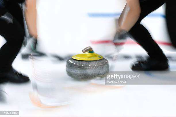 Japan's Yumi Suzuki brushes in front of the stone with her teammate during the curling women's bronze medal game between Britain and Japan during the...