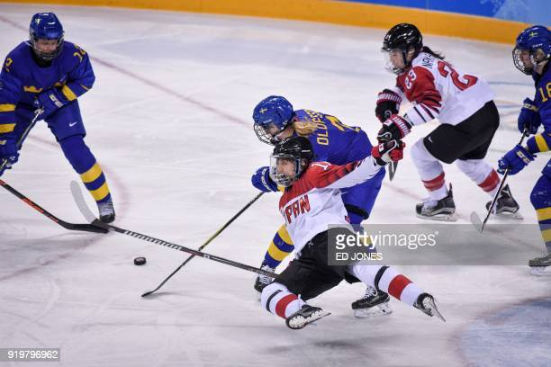 Japan's Yurie Adachi falls against Sweden's Johanna Olofsson in the women's classifications ice hockey match between Sweden and Japan during the...