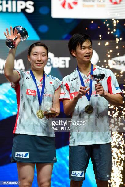 Japan's Yuta Watanabe and Japan's Arisa Higashino celebrate on the podium with their trophies after winning the mixed doubles final against China's...
