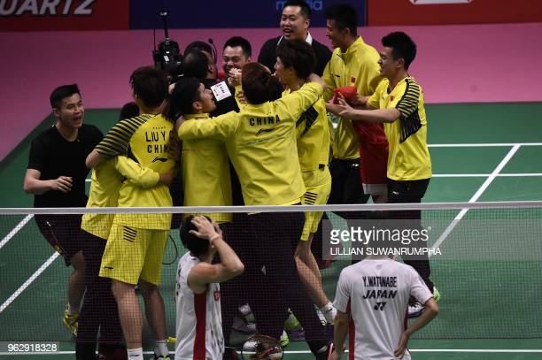 Japan's Yuta Watanabe and Keigo Sonoda watch as China's team members celebrate at the end of the mens double final match at the Thomas Cup badminton...