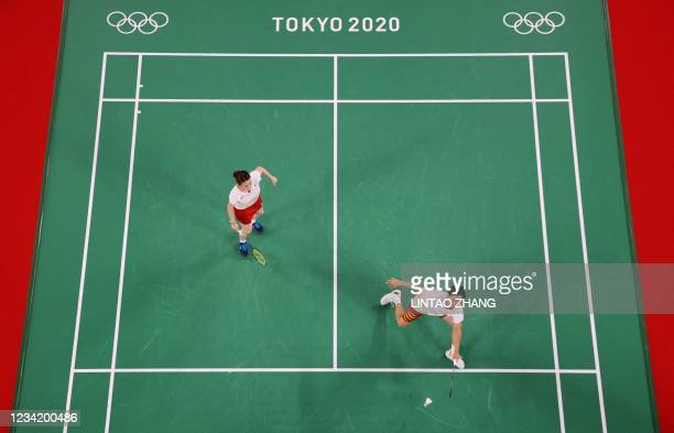 Japan's Yuta Watanabe hits a shot next to Japan's Arisa Higashino in their mixed doubles badminton group stage match against Indonesia's Praveen...