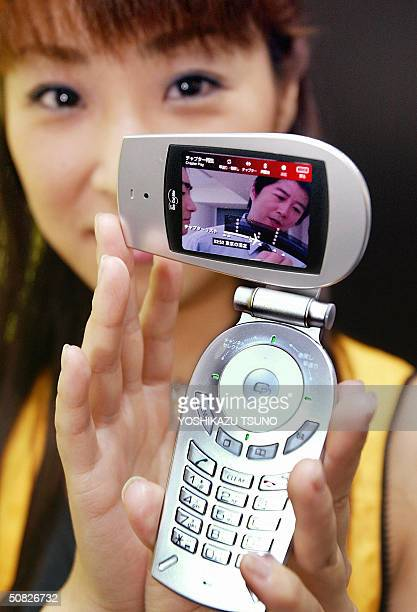 Japanse mobile communication giant NTT DoCoMo employee displays a prototype model of a TV phone handset 'ONQ ' which can receive digital bradcasting...