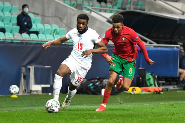 Japhet Tanganga of England runs with the ball whilst under pressure from Gedson Fernandes of Portugal during the 2021 UEFA European Under-21...