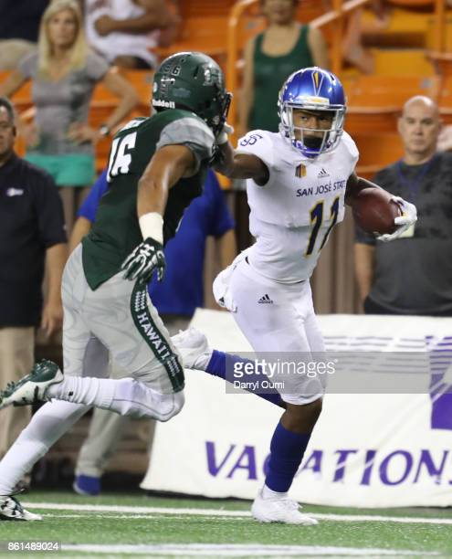 JaQuan Blackwell of the San Jose State Spartans stiff arms Kalen Hicks of the Hawaii Rainbow Warriors during the third quarter of their game at Aloha...