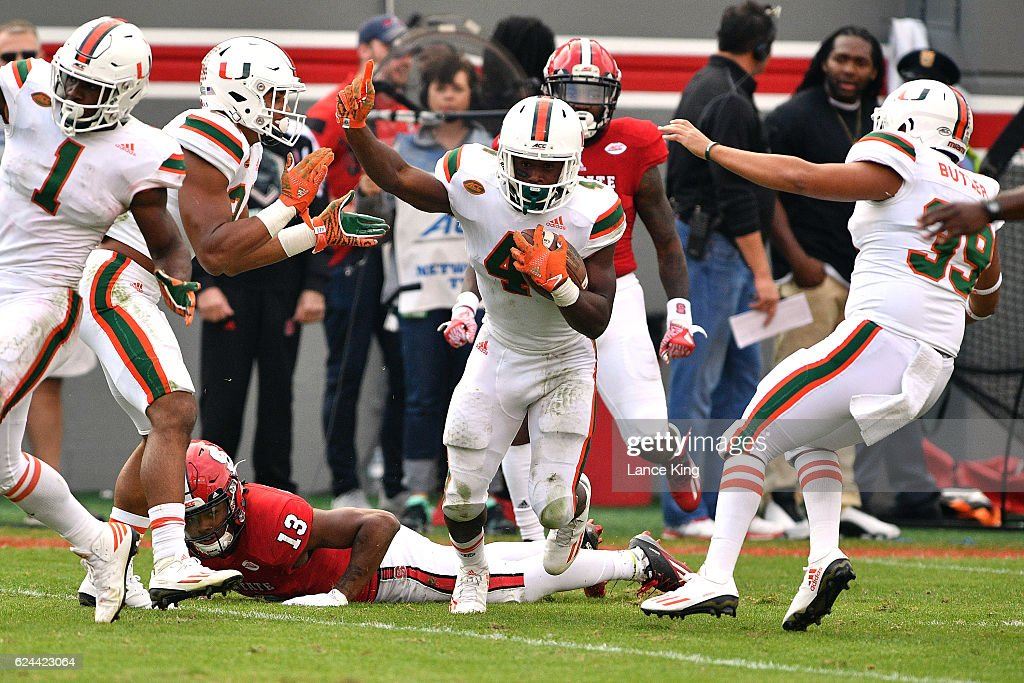 Jaquan Johnson #4 of the Miami Hurricanes celebrates following a fumble recovery against Bra'Lon Cherry #13 of the North Carolina State Wolfpack at Carter-Finley Stadium on November 19, 2016 in Raleigh, North Carolina. Miami won 27-13.