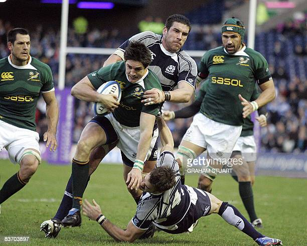 Jaque Fourie of South Africa tackled by Thom Evans and Jim Hamilton of Scotland during an international test match between Scotland and South Africa...