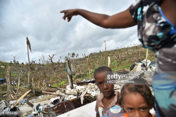 Jaqueline and her children stand on the site of her destroyed house amid destroyed vegetation from Hurricane Matthew in the area of Chabet commune of...