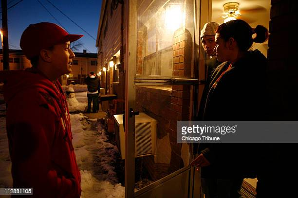 Jaqueline Irizarry right and her son Angel talk with fellow plant employee at the back door of their apartment December 19 in Rantoul Illinois The...