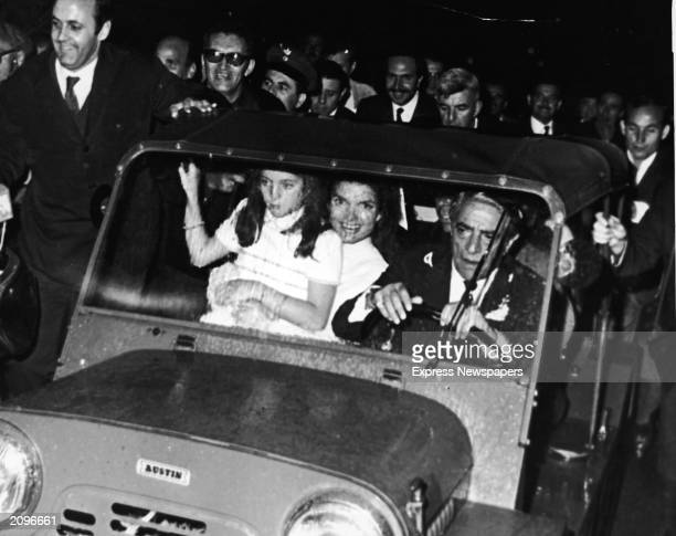 Jaqueline Kennedy Onassis sits with her daughter, Caroline Kennedy, on her lap while driving away from the chapel with her new husband, Greek...