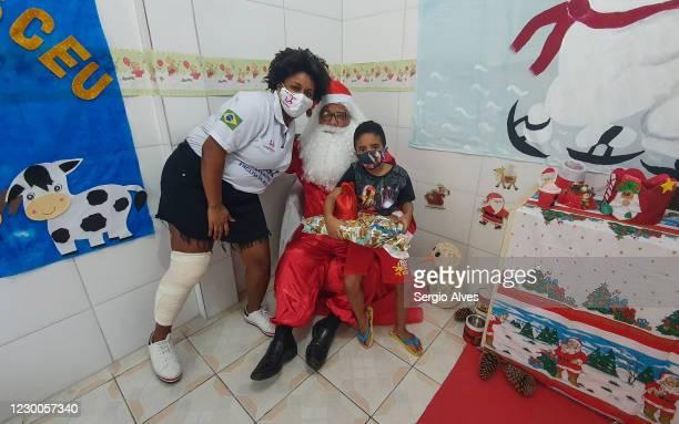 Jaqueline Laureano and Thiago Venancio pose with a person dressed as Santa Claus at the Christmas party at Uniao de Mulheres Pro Melhoramentos da...