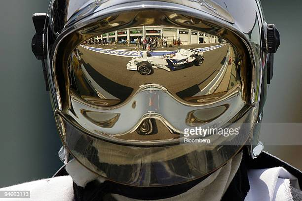 Jaques Villeneuve driver for BMW Sauber is seen in a reflection on a firemen's helmet during the first practice day for the Formula 1 GP of France on...