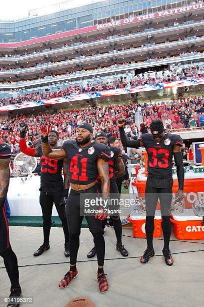 Jaquiski Tartt Antoine Bethea and Rashard Robinson of the San Francisco 49ers hold their fist in the air during the anthem on the sideline prior to...