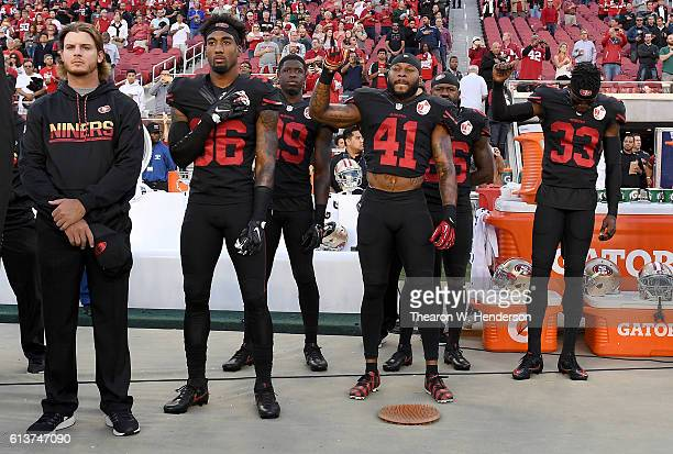 Jaquiski Tartt Antoine Bethea Tramaine Brock and Rashard Robinson of the San Francisco 49ers hold their fists up in protest during the national...