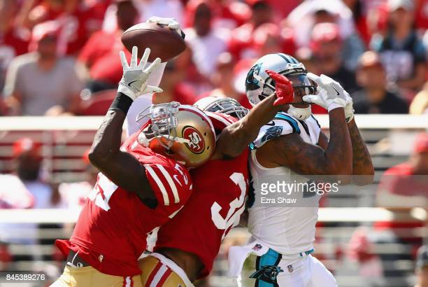 Jaquiski Tartt of the San Francisco 49ers intercepts the pass intended for Kelvin Benjamin of the Carolina Panthers while Dontae Johnson of the San...