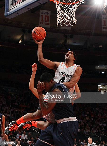 Jaquon Parker of the Cincinnati Bearcats goes to the basket against Henry Sims of the Georgetown Hoyas during the quarterfinals of the Big East Men's...