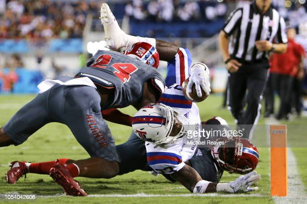 Jaqwis Dancy of the Louisiana Tech Bulldogs dives into the endzone for a touchdown against the Florida Atlantic Owls during the first half at FAU...