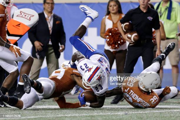 Jaqwis Dancy of the Louisiana Tech Bulldogs is tackled by Brandon Jones of the Texas Longhorns and Josh Thompson in the second half at Darrell K...
