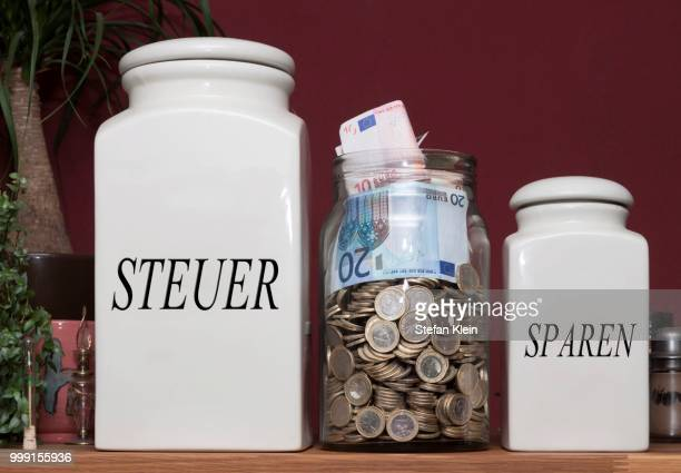 jar containing money and jars with the signs --steuer-- and --sparen--, german for --taxes-- and --savings--, on a kitchen shelf, germany - fiscal policy stock pictures, royalty-free photos & images