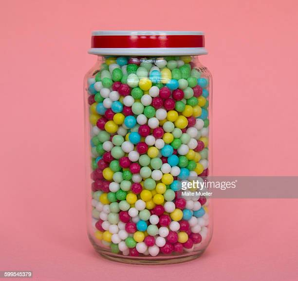 Jar full of candies against pink background