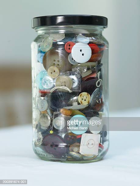 Jar of buttons on table, close-up (focus on jar)