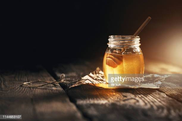 jar of camomile honey on black background - honey stock pictures, royalty-free photos & images
