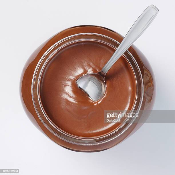 Jar of chocolate cream on white background with spoon inside