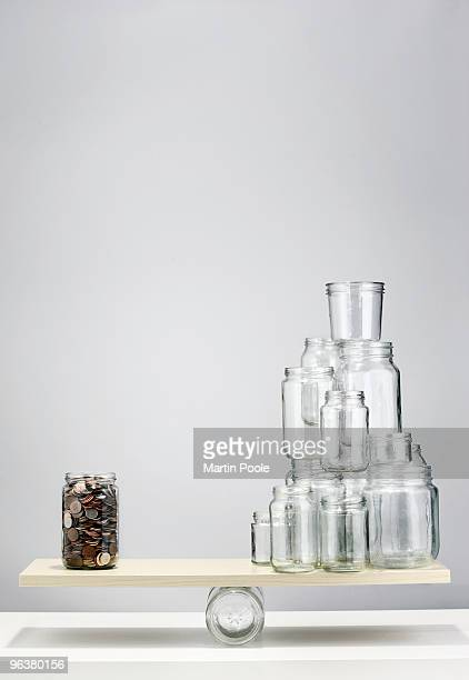 jar of coins balancing on seesaw with empty jars