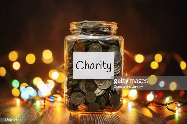 jar of coins for charity against christmas lights background - charity benefit stock pictures, royalty-free photos & images