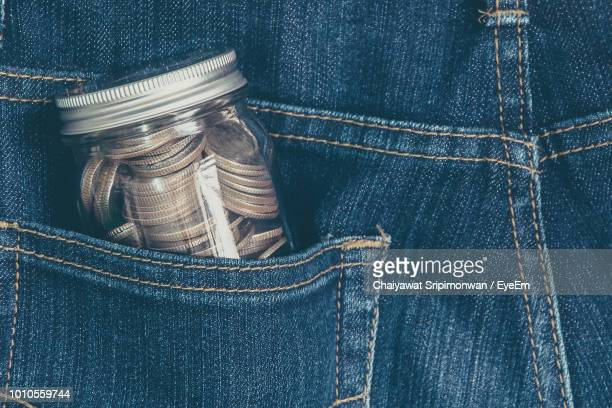 jar of coins in jeans pocket - silver trousers stock pictures, royalty-free photos & images