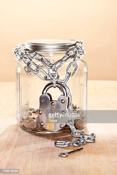 Jar of coins with heavy duty lock around it