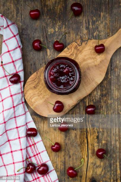 jar of homemade cherry jam and cherries on wood - larissa veronesi stock pictures, royalty-free photos & images